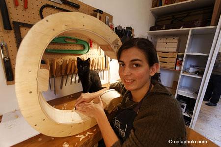 Luthier dans son atelier travaillant sur un violoncelle